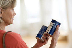 woman reading labels on cans